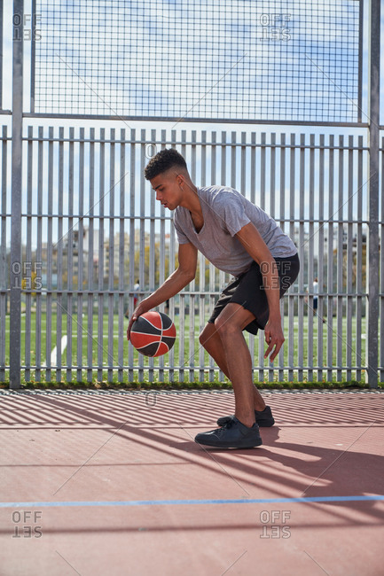 Determined ethnic male player practicing with basketball on modern court in summer while looking down