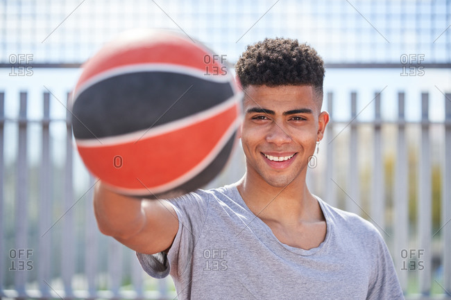 Young determined African American male player standing with basketball on sports ground and looking at camera