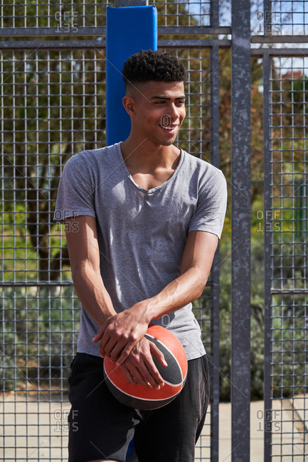 Calm African American player standing with basketball and leaning on metal grid on playground while looking away