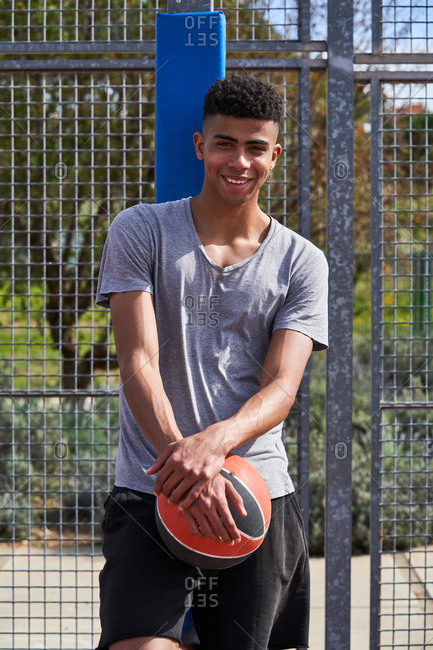 Calm African American player standing with basketball and leaning on metal grid on playground while looking at camera