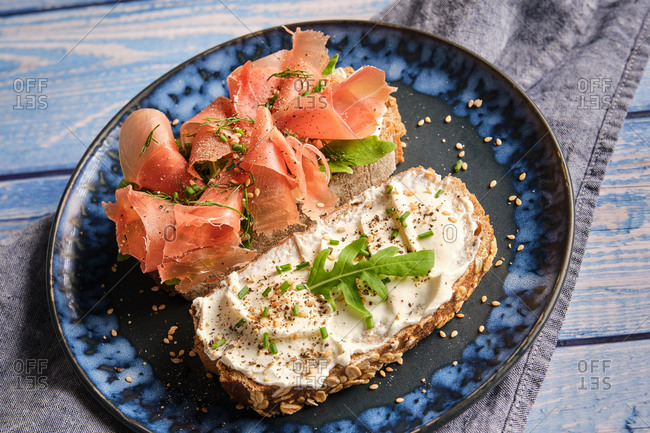 Appetizing toasts made with wholegrain bread with cream cheese and sliced ham garnished with fresh green herbs served on plate on wooden table for healthy breakfast