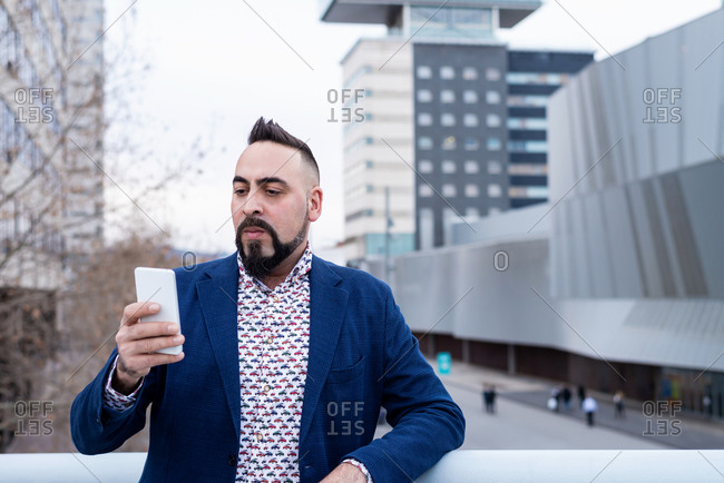 Bearded man leaning on railing outdoors while using a smartphone