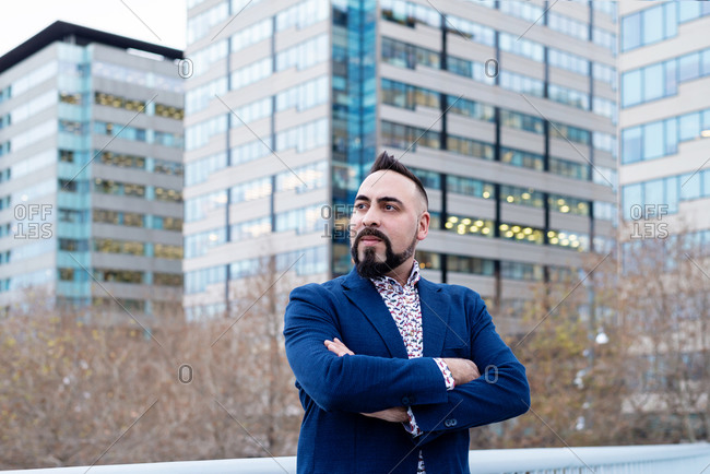 Bearded businessman standing with crossed arms in financial district while looking away