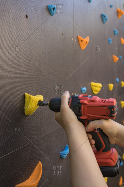 Unrecognizable mechanic using electric screwdriver and fixing grips on climbing wall in gym