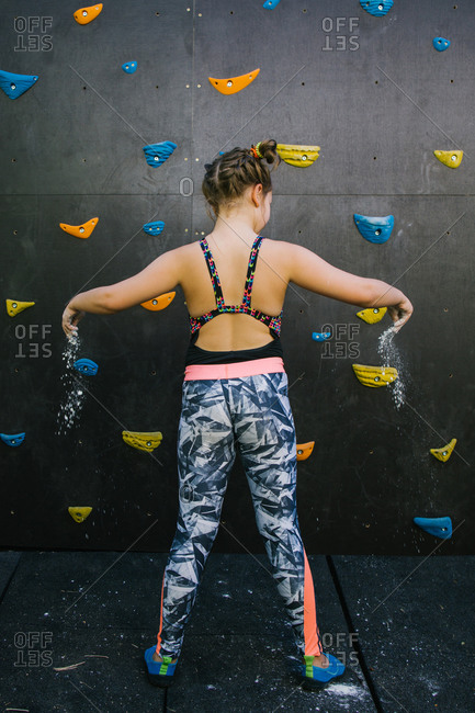 Back view of determined child in sportswear applying chalk on palms before climbing wall in gym