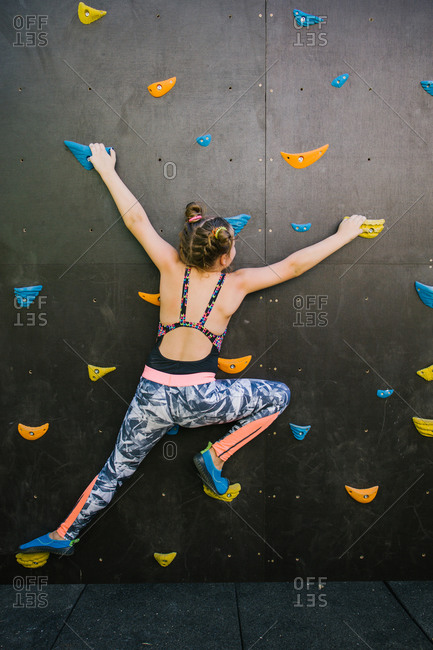 Back view of anonymous child in sportswear climbing wall with artificial rocks while training in gym and enjoying weekend