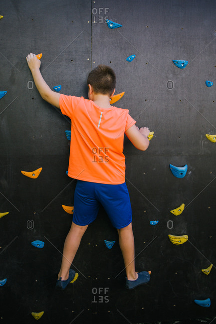 Back view of unrecognizable fearless child balancing on grips and climbing wall while practicing bouldering in gym