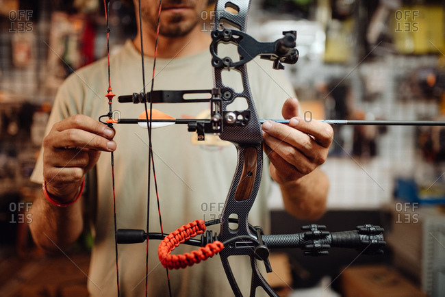 Cropped unrecognizable busy male hunter adjusting compound bow with arrow while standing in garage and preparing for shooting