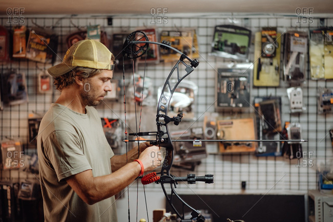 Side view of busy male hunter adjusting compound bow with arrow while standing in garage and preparing for shooting