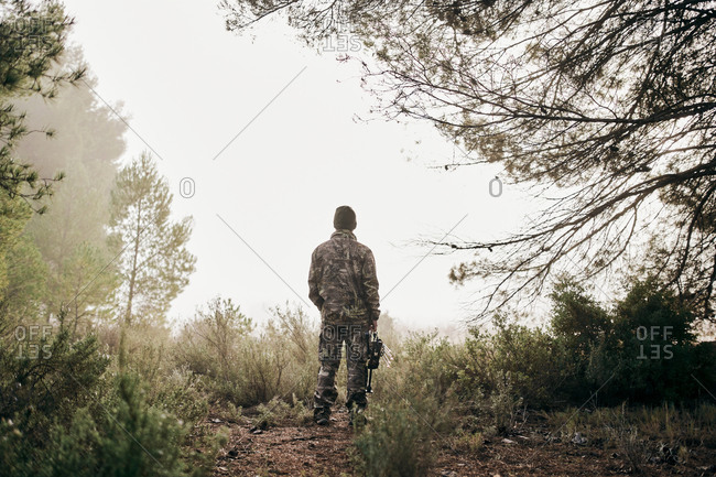Back view of unrecognizable man in camouflage standing with compound bow in forest and looking away during hunting