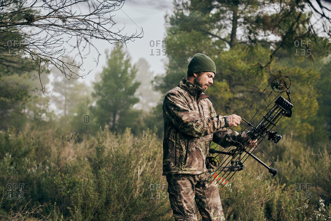 Side view of serious male hunter adjusting compound bow with arrow while preparing for hunting in woods in autumn