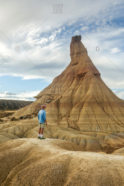 Back view of male tourist in summer wear standing on dried soil in Bardenas Reales and enjoying amazing view of natural rocky formation