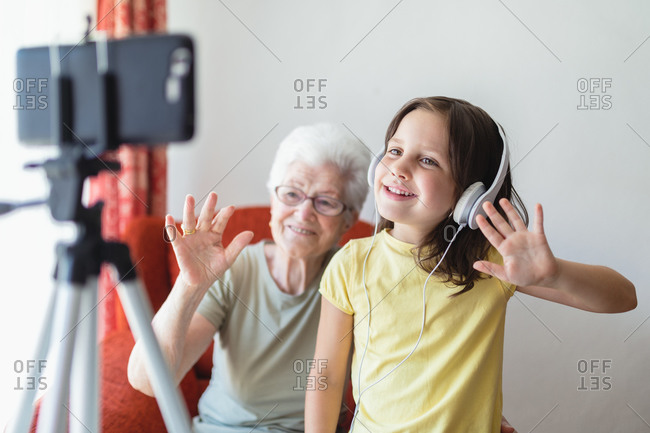 Smiling senior woman and girl sitting in living room together and having video call on smartphone
