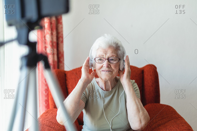 Content senior lady in headphones sitting in cozy armchair at home and enjoying songs while looking away