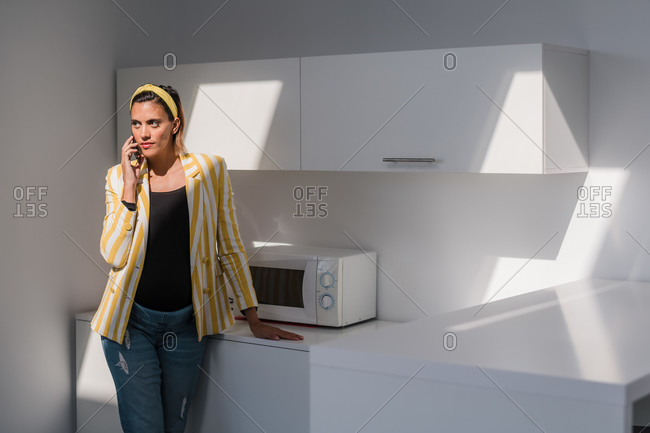Young pregnant female in trendy striped jacket and jeans talking on smartphone while standing in modern kitchen with white furniture and microwave oven