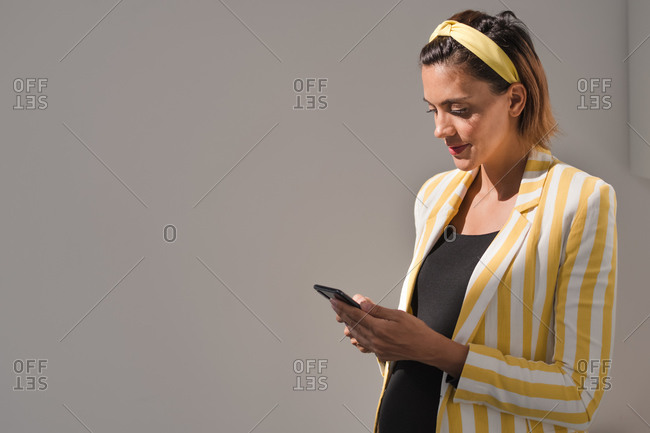 Positive pregnant female in trendy white and yellow striped jacket messaging on mobile phone while standing against gray background