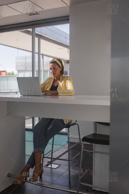 Positive busy pregnant female remote worker in stylish striped jacket and headband sitting at table and browsing laptop while working on project at home