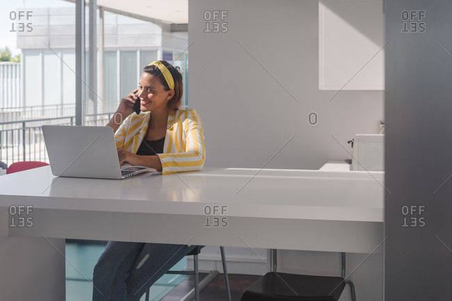 Modern female freelancer in stylish outfit sitting at counter with laptop and discussing details of project via mobile phone while working in contemporary workspace