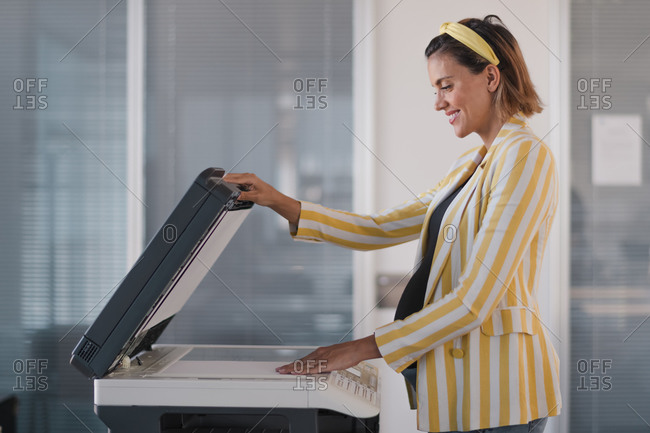 Side view of optimistic pregnant businesswoman in stylish outfit putting paper sheet on photocopier while working in modern workspace