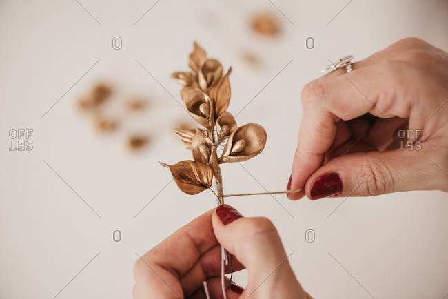 High angle of anonymous female artisan creating decorative flowers and wrapping twig with thread while working in workshop