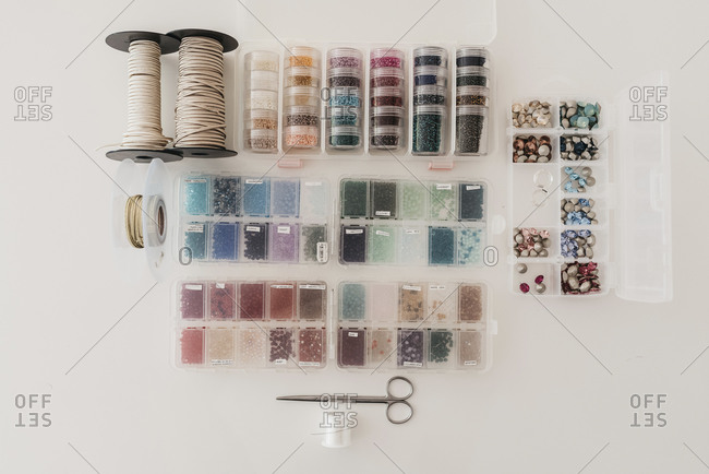 Top view of colorful beads in plastic containers arranged on table with threads and scissors