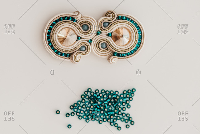 Traditional handmade soutache bijouterie with shiny beads placed on table in bright workshop