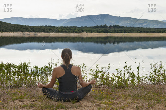 Full length back view of unrecognizable female in sportswear meditating in lotus pose with Gyan mudra gesture on lake shore against mountains in summer morning