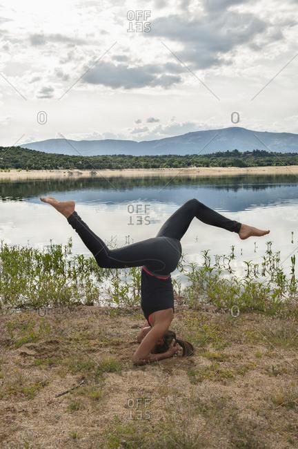 Full body side view of slim female in sportswear doing Salamba Sirsasana yoga pose variation during practice on lake shore