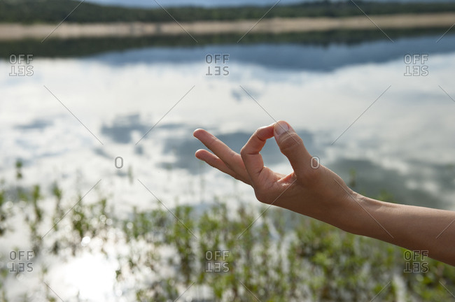 Crop unrecognizable female with Gyan Mudra hand gesture practicing yoga meditation on shore of calm lake in nature