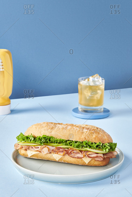 Appetizing sandwich with ham and fresh lettuce served on plate on table in cafeteria