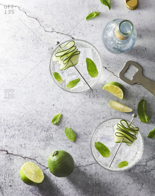 From above of refreshing Mojito cocktails in glasses with ice cubes arranged on table with lime slices