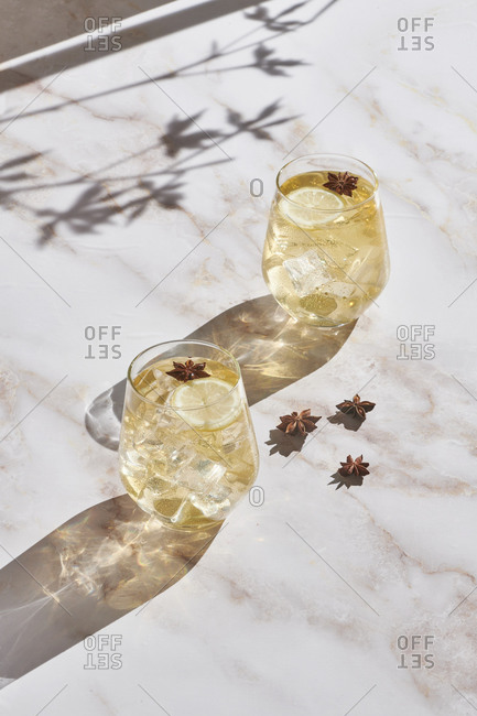 High angle of delicious cocktails with lemon slices and ice cubes garnished with star anise and served on marble table