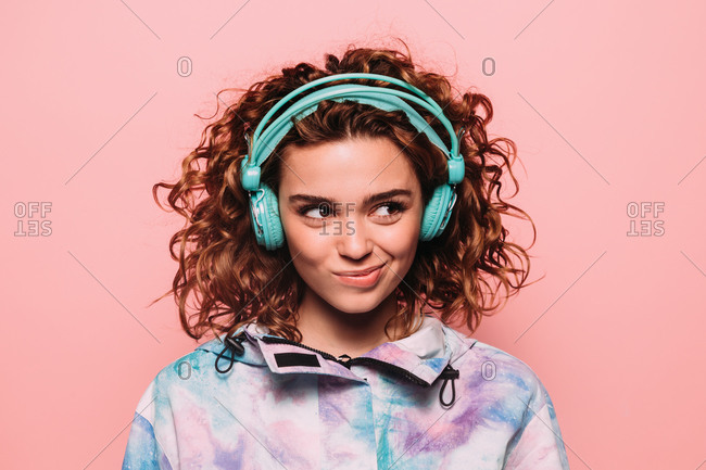 Studio portrait of curly redhead girl over pink background. She is wearing green headphones and looking away with funny gesture