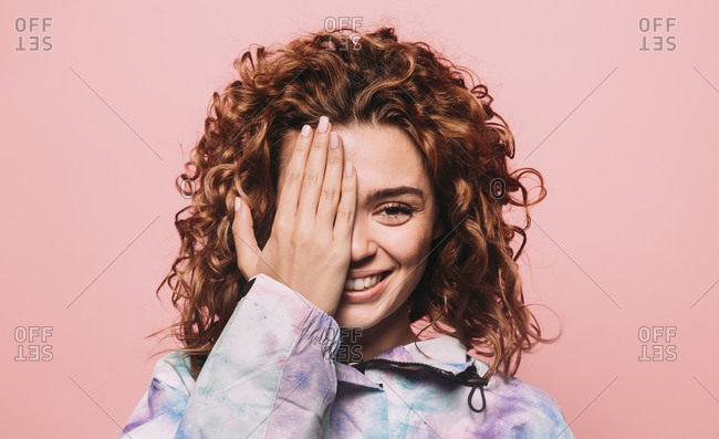 Studio portrait of curly redhead girl smiling at camera over pink background covering one eye with hand