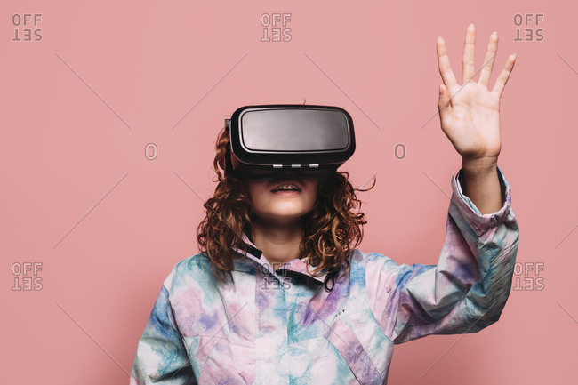 Portrait of redhead girl playing with VR glasses over pink background