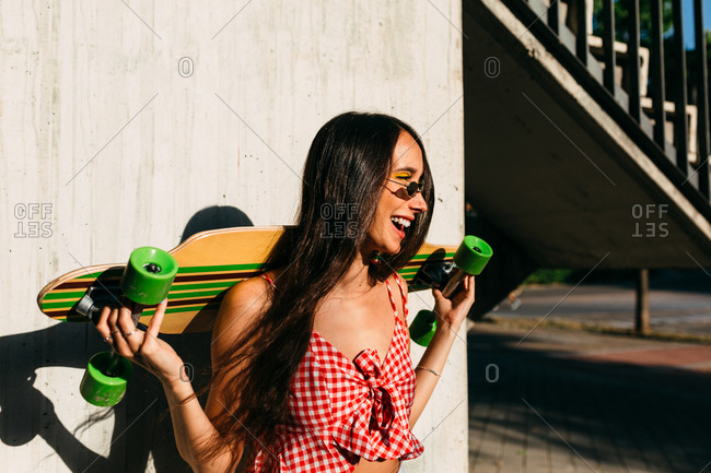 Portrait of brunette girl with long hair holding a long board and looking away in front of white background