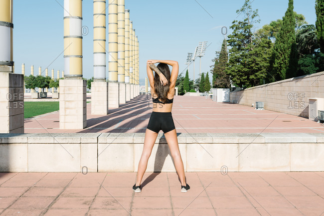 Full body back view of unrecognizable slim female in sportswear stretching shoulders while warming up before fitness workout on urban square
