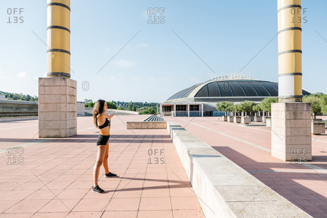 Full body side view of slim female in sportswear stretching arms while warming up before fitness workout on urban square