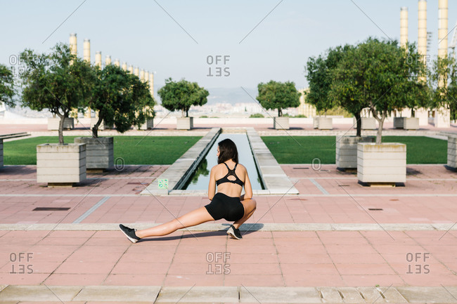 Full body back view of unrecognizable slim female in sports bra and shorts doing lunges exercise while training alone on paved square in city