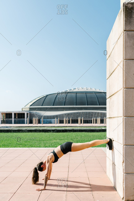 Full body side view of unrecognizable athletic female in sportswear doing feet on wall push ups near concrete building on city square