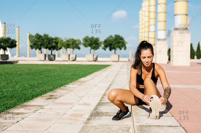 Full body of slim female athlete in sportswear sitting on pavement and tying laces on sneakers while preparing for running in summer day in city