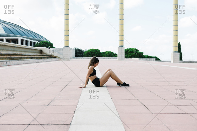 Full body side view of young slim female in sports top and shorts sitting on paved square near modern building and resting after fitness training
