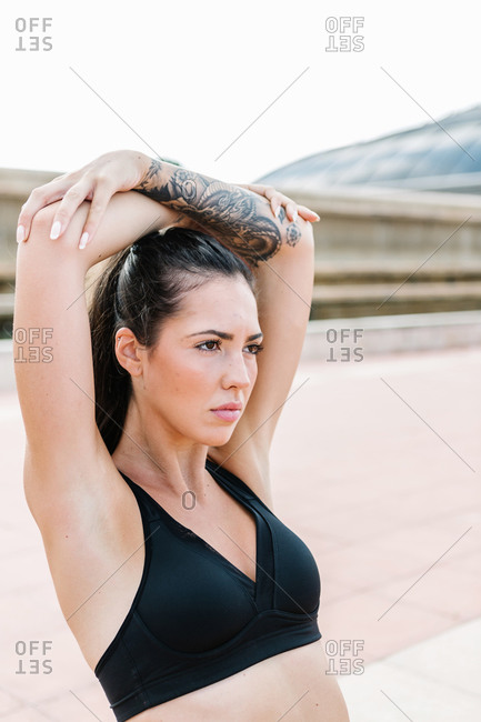 Side view of focused slim female in sportswear stretching shoulders while warming up before fitness workout on urban square
