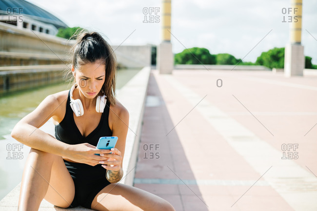 Fit female with tattoo on arm and headphones on neck dressed in black sports bra and shorts browsing mobile phone while sitting on stone border and relaxing after fitness workout on street