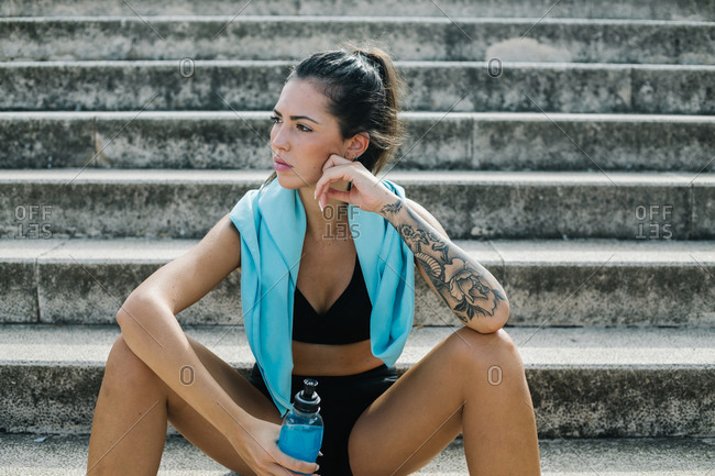 Low angle of young fit female athlete in activewear with towel on neck sitting on stone stairway resting and holding a water plastic bottle while relaxing after fitness training on street