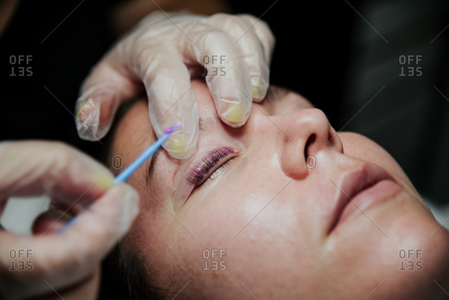 Closeup of crop unrecognizable cosmetician in latex gloves applying purple chemical solution on eyelid of female client during eyelashes lifting procedure in salon