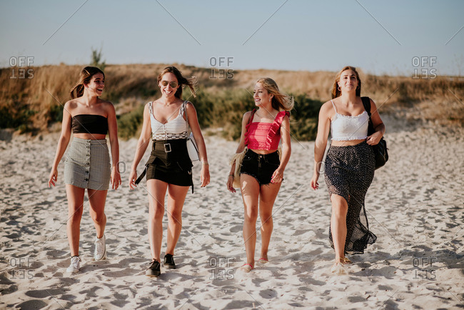 Full body cheerful young girlfriends in casual clothes walking together on sandy beach and chatting happily while spending summer holidays together