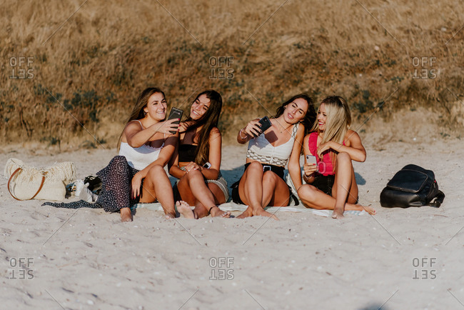 Group of smiling young ladies in casual clothes sitting on sandy beach and taking selfie with mobile phones while enjoying summer holidays together