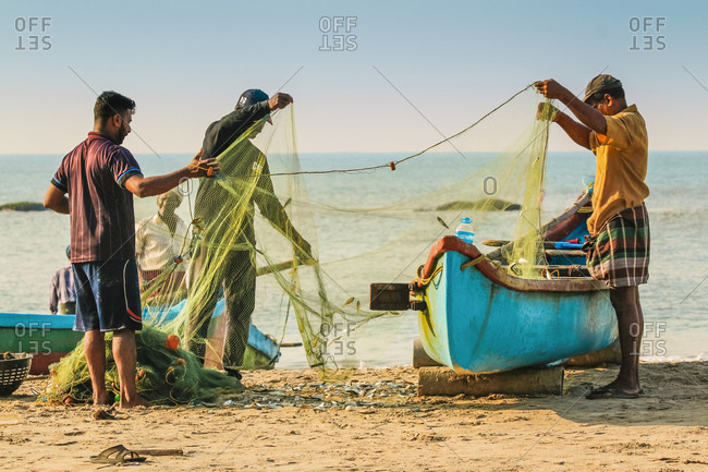 October 24, 2017: Fishermen cleaning net at beautiful Kizhunna Beach, south of Kannur on the Keralan north coast, Kizhunna, Kannur, Kerala, India, Asia