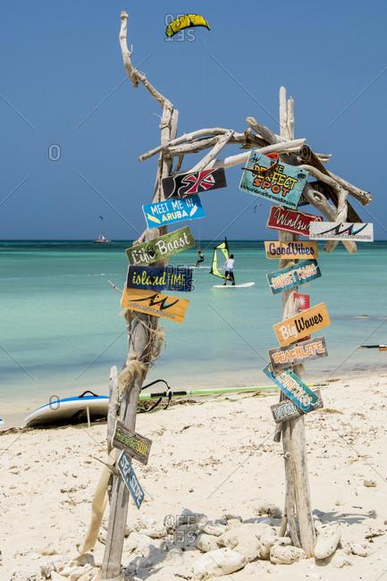 March 15, 2018: Windsurfing and signs at Hadicurari Beach, Aruba, ABC Islands, Dutch Antilles, Caribbean, Central America